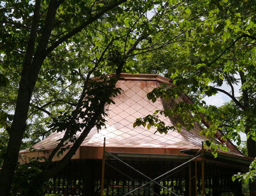 Diamond pattern copper shingles installed on lakeside gazebo roof.